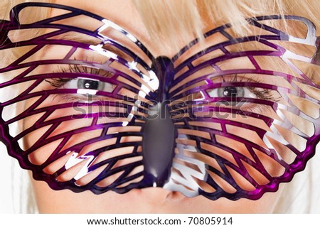 Closeup portrait of a cute young girl with carnival mask on her face - stock photo