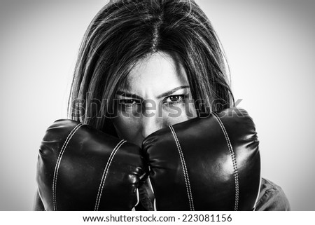 Closeup portrait of a determined female boxer. Confident, fearless and furious modern business woman with boxing gloves in isolated over white background - stock photo