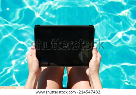 Closeup portrait of a female hands using tablet computer in swimming pool - stock photo