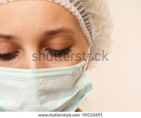 Closeup portrait of a female nurse or a doctor looking down, isolated on white background