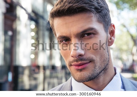 Closeup portrait of a handsome businessman outdoors looking at camera - stock photo