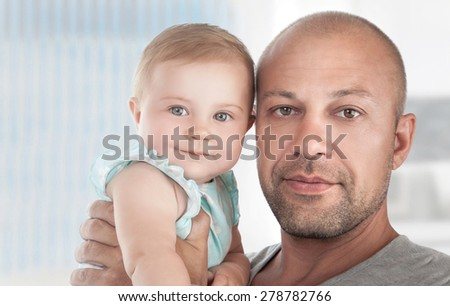 Closeup portrait of a handsome dad with cute little daughter on hands, spending time at home, happy fathers day theme