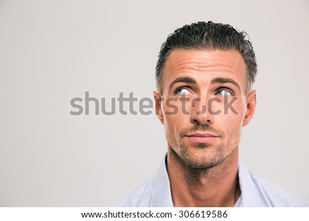 Closeup portrait of a handsome man looking away at copyspace over gray background - stock photo
