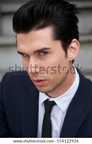 Closeup portrait of a handsome young man in suit and tie  - stock photo