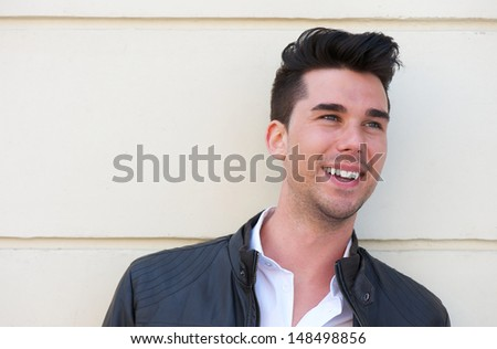 Closeup portrait of a handsome young man smiling outdoors - stock photo