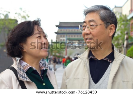 Closeup portrait of a happy aged Chinese couple looking at each other - stock photo