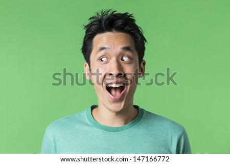 Closeup portrait of a happy Asian/Chinese man looking to left. Against green background.