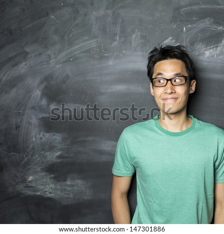 Closeup portrait of a happy Asian/Chinese man looking to left. Standing next to a blackboard. - stock photo