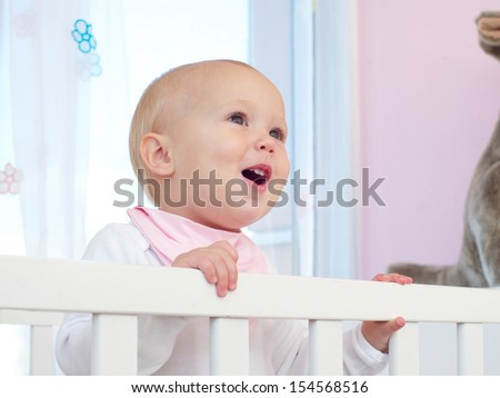 Closeup portrait of a happy baby smiling in crib