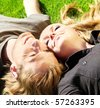 Closeup portrait of a happy couple lying on the grass - stock photo