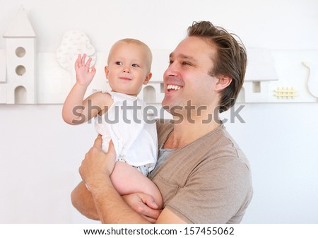 Closeup portrait of a happy father holding cute baby indoors - stock photo