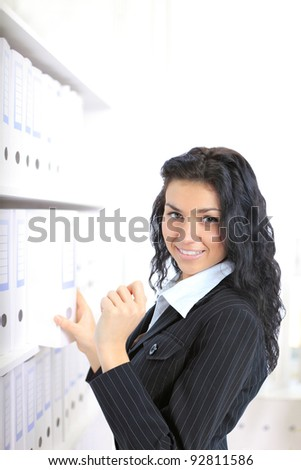 Closeup portrait of a happy young business woman,choose the document  in her office - stock photo