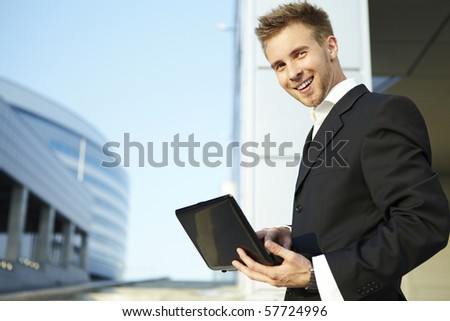 Closeup portrait of a happy young businessman using laptop on street - stock photo