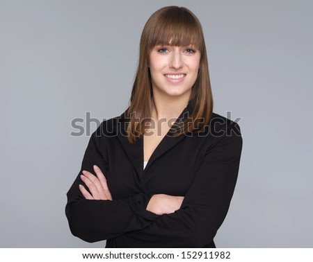 Closeup portrait of a happy young businesswoman isolated on gray background - stock photo