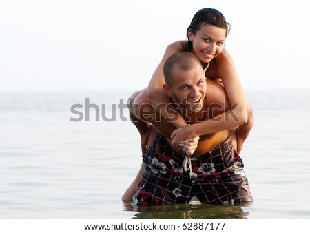 Closeup portrait of a happy young couple in sea - stock photo