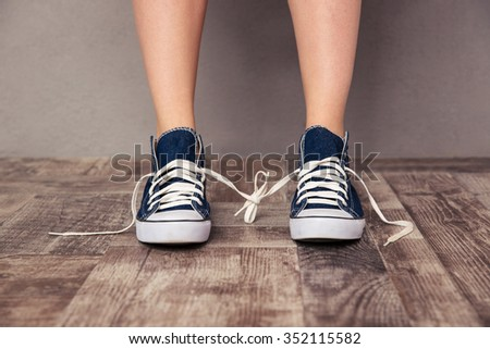 Closeup portrait of a human legs in sneakers tied with each other