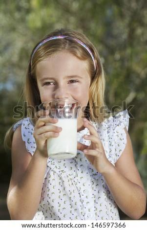 Closeup portrait of a little girl drinking milk outdoors - stock photo