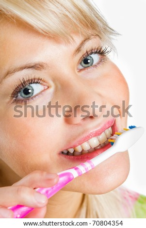 Closeup portrait of a lovely young female cleaning her teeth - stock photo