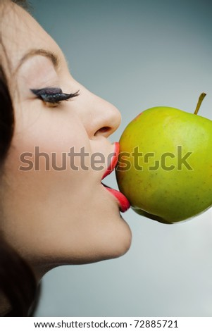 Closeup portrait of a lovely young girl kissing a green apple standing on half-face against blue background - stock photo
