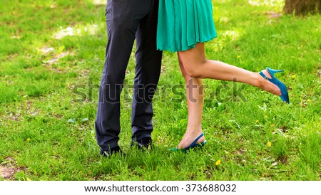 Closeup portrait of a Male and female legs during a date - stock photo