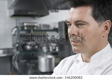 Closeup portrait of a male chef looking away in kitchen - stock photo