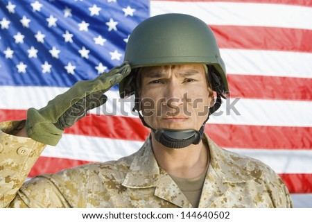 Closeup portrait of a male soldier saluting in front of United States flag - stock photo