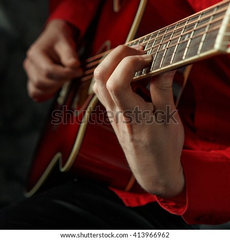 Closeup portrait of a man in a red shirt, playing on a red acoustic guitar. Shallow depth of field.