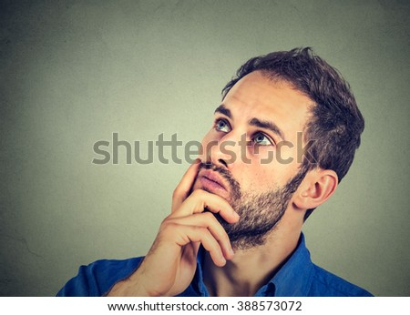 Closeup portrait of a man resting chin on hand thinking daydreaming, staring thoughtfully upwards, copy space to left, isolated on gray wall background. Human emotions feelings  reaction  - stock photo