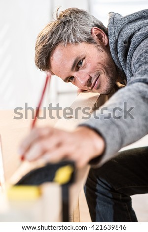 Closeup portrait of a man taking measurements on a piece of wood, the focus is on his full mastery glance