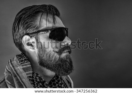 Closeup portrait of a  man with beard wearing a traditional arabic scarf and black glasses over gray background - stock photo