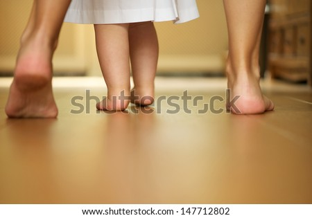 Closeup portrait of a mother teaching baby to walk indoors - stock photo