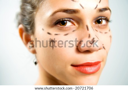 Closeup portrait of a pretty Caucasian woman's face marked with lines for facial cosmetic surgery - stock photo