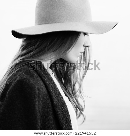 Closeup portrait of a pretty girl walking down lakeside. Profile to camera. Wearing hat and jacket. Outside - stock photo