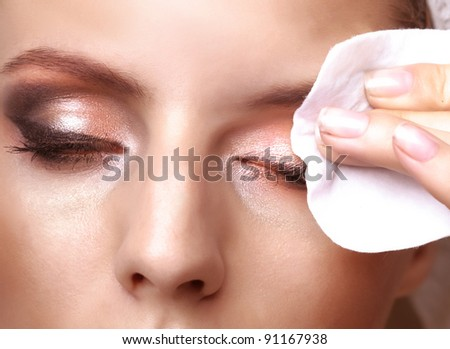 Closeup portrait of a pretty young woman using cotton on closed eyes - stock photo