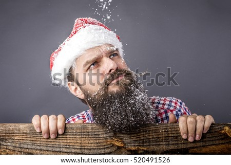 Closeup portrait of a sad bearded man with santa cap looking up over gray. Christmas time
