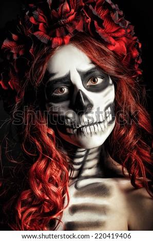 Closeup portrait of a sad young girl with muertos makeup (sugar skull) - stock photo