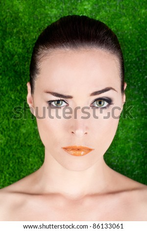 Closeup portrait of a serious beautiful woman raising an eyebrow on green background - stock photo