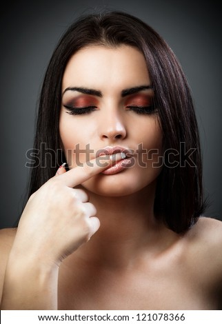 Closeup portrait of a sexy brunette with finger in mouth