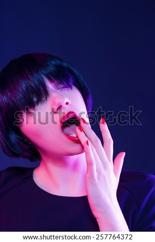 Closeup portrait of a sexy brunette with finger in mouth - stock photo