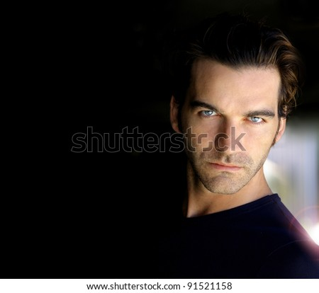 Closeup portrait of a sexy male model with lots of dark copy space - stock photo