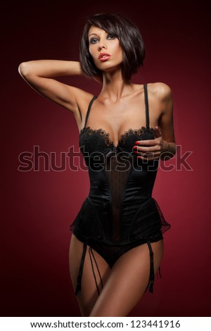 closeup portrait of a sexy young woman in black corset and touching her breast against red wine background - stock photo
