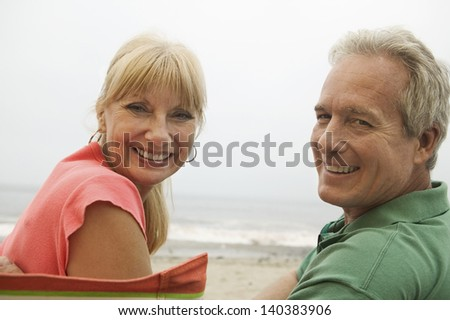 Closeup portrait of a smiling middle aged couple at the beach - stock photo