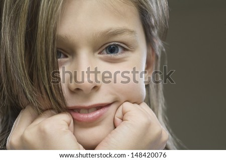 Closeup portrait of a smiling young girl against gray background - stock photo