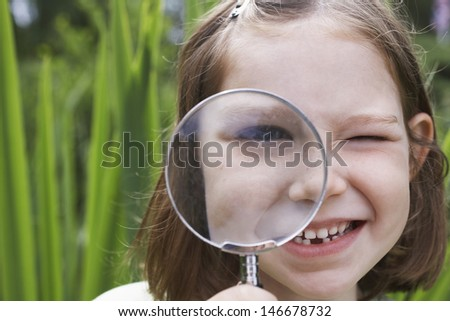 Closeup portrait of a smiling young girl looking through magnifying glass - stock photo