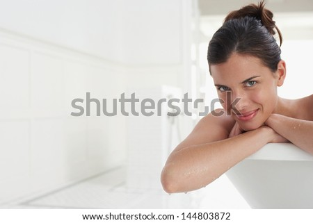 Closeup portrait of a smiling young woman relaxing in bathtub - stock photo