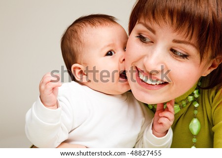 Closeup portrait of a sweet baby kissing  mother - stock photo