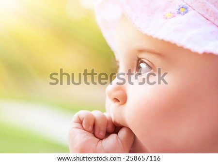 Closeup portrait of a sweet little baby girl in bright light of sunny day, cute kid face over blur green background, child enjoying outdoors, innocence and happiness - stock photo