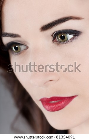 Closeup portrait of a thoughtful beautiful middle aged woman's green eyes and red lips