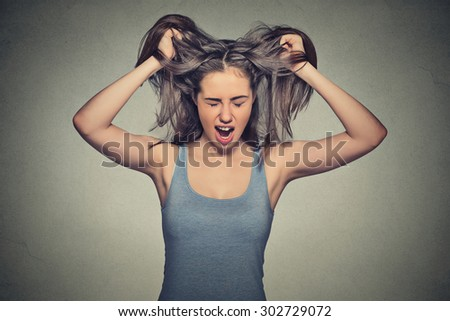 Closeup portrait of a very angry woman screaming acting out isolated on gray wall background  - stock photo