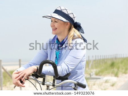 Closeup portrait of a woman enjoying bike ride on a summer day - stock photo